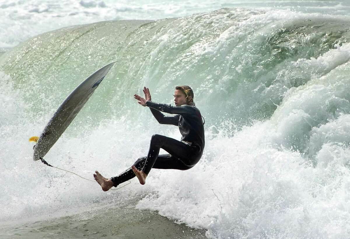 A surfer loses his board as he rides a wave in Huntington Beach, Calif., on Sunday, Sept. 7, 2014. Hurricane Norbert slumped to tropical storm force off of Mexico's Baja California peninsula on Sunday after pounding fishing villages and damaging more than 1,000 homes while kicking up dangerous surf farther north along the California coast.