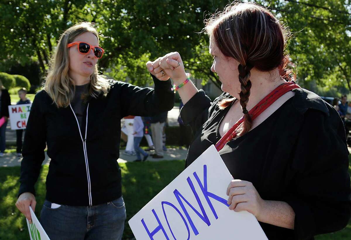 Barbara Webb, 33, of Madison Heights, left, gets a bump from her long time friend Lauren Lennon, 31, of Fraser during a protest on behalf of Webb Sunday Sep. 7, 2014. Webb was fired from Marian High School after administrators at the Catholic all-girl high school were made aware of her nontraditional pregnancy.