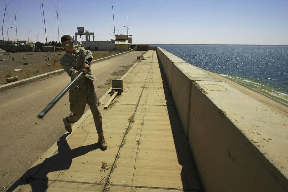 FILE - In this Sunday, May 29, 2005 file photo, U.S. Marine Lance Cpl. Andrew Bickerstaff of Satellite Beach, Florida, uses a tent pole to bat a rock off the Haditha Dam where his unit is based, 220 kilometers (140 miles) northwest of Baghdad. The U.S. military launched airstrikes Sunday around Haditha Dam in western Iraq, targeting Islamic State insurgents there for the first time in a move to prevent the group from capturing the vital dam. (AP Photo/Jacob Silberberg, File) Photo: Jacob Silberberg, STF / AP