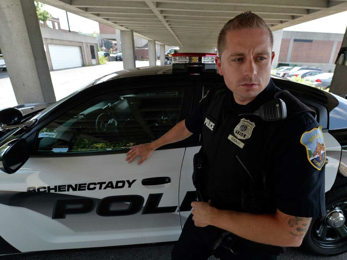 Schenectady Police officer Sam Gonzalez stands by his police cruiser Friday afternoon Sept. 5, 2014 outside headquarters in Schenectady, N.Y. (Skip Dickstein/Times Union)