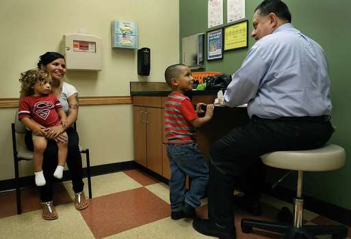 Dr. Juan Para, right, is questioned by five year old Angel Martinez, center, during a pediatric check up at CentroMed Southside Clinic. Angel's mother Felicia Martinez, left, holds Israel Villarreal, another son. Thursday, Aug. 28, 2014. Photo: San Antonio Express-News / © 2012 San Antonio Express-News
