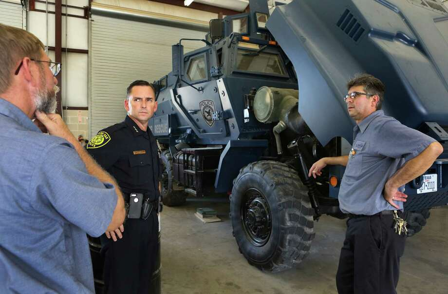City of Live Oak Police Chief Ken Evans, center, talks with Fleet Maintanence Supervisor, William Weidner, left, and Mechanic Tony Barela, right,  as they look at the police department's military surplus MRAP which will be part of Alamo Area Metro SWAT.  The vehicle is currently waiting on parts for a repair in the city's garage.  Friday, Aug. 5, 2014. Photo: San Antonio Express-News / ©2013 San Antonio Express-News