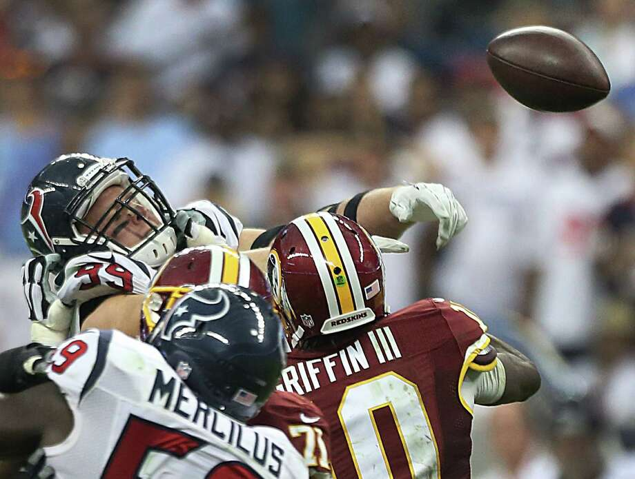 J.J. Watt (99) had one of the most well-rounded games of his career, including this knockdown of a Robert Griffin III pass. Photo: Brett Coomer, Staff / © 2014  Houston Chronicle