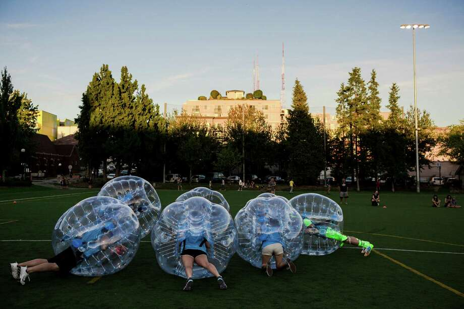 "Encased in bouncy, blue orbs, teams huddled up as best their rotund shape allowed them before a match at Seattle's first ""Bubble Futbol"" - or soccer - tournament Sunday, September 7, 2014, at Cal Anderson Park in Capitol Hill in Seattle, Washington. The unlikely sport originated in Europe and is quickly sweeping the U.S., with a recent spotlight on ÒThe Tonight Show with Jimmy Fallon.Ó The event was put on by Seattle-local nonprofit ""The World is Fun"" as a celebration of the organization's fifth anniversary. Photo: JORDAN STEAD, SEATTLEPI.COM / SEATTLEPI.COM"