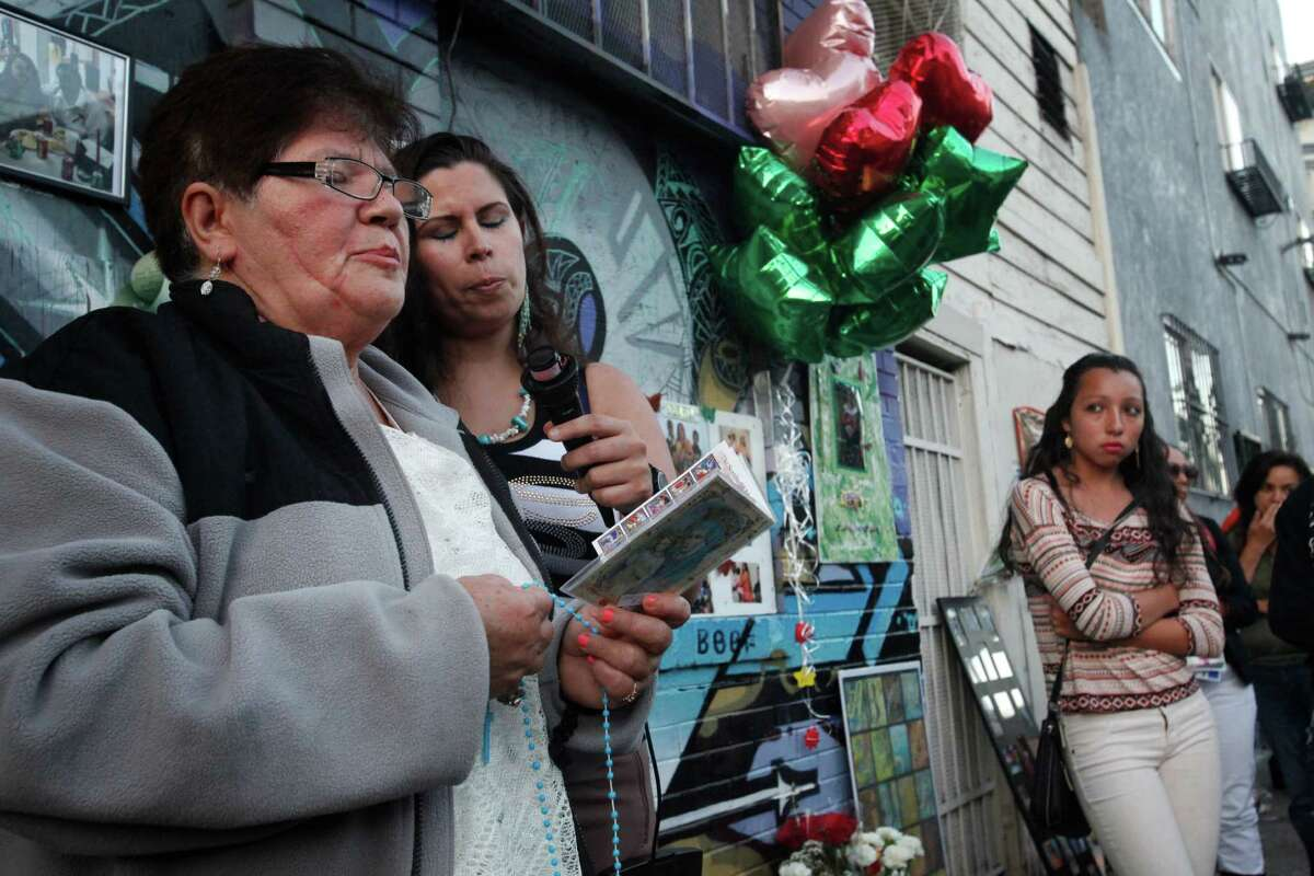 Victoria Morales, left, the grandmother of Williams, and his Aunt Ruth Morales lead the rosary during a vigil held in honor of Rashawn Williams, 14, at the corner where he was stabbed to death last week on 26th and Folsom Sept. 7, 2014 in San Francisco, Calif.