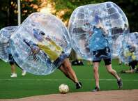 """Players push downfield, often to collide, while encased in bouncy, blue orbs as part of Seattle's first """"Bubble Futbol"""" - or soccer - tournament Sunday, September 7, 2014, at Cal Anderson Park in Capitol Hill in Seattle, Washington. The unlikely sport originated in Europe and is quickly sweeping the U.S., with a recent spotlight on ÒThe Tonight Show with Jimmy Fallon.Ó The event was put on by Seattle-local nonprofit """"The World is Fun"""" as a celebration of the organization's fifth anniversary."""