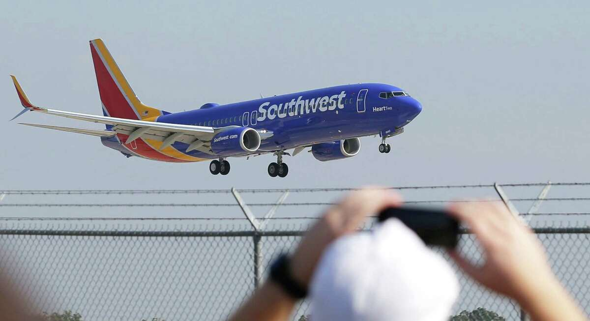 A Southwest Airlines plane with a new paint job flies over Love Field Monday, Sept. 8, 2014, in Dallas. The change comes in a year during which 43-year-old Southwest has begun international flights, expanded in New York and Washington, and is freed from longtime government limits on its Dallas schedule. (AP Photo/LM Otero)
