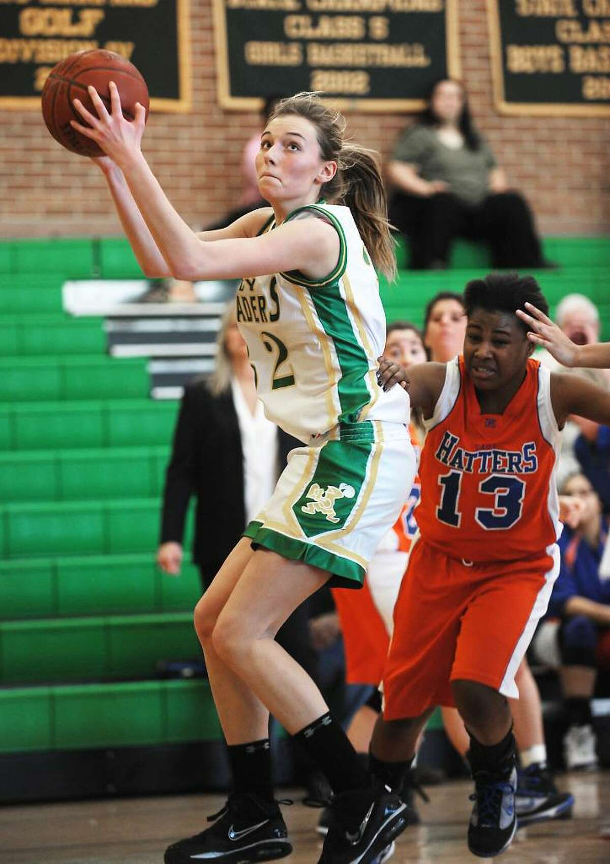 Trinity Catholic's Cayleigh Griffin goes in for a shot against Danbury's Jasmine Holmes in the quarterfinals of the FCIAC girls basketball championship in Stamford, Conn. on Saturday, Feb. 20, 2010.