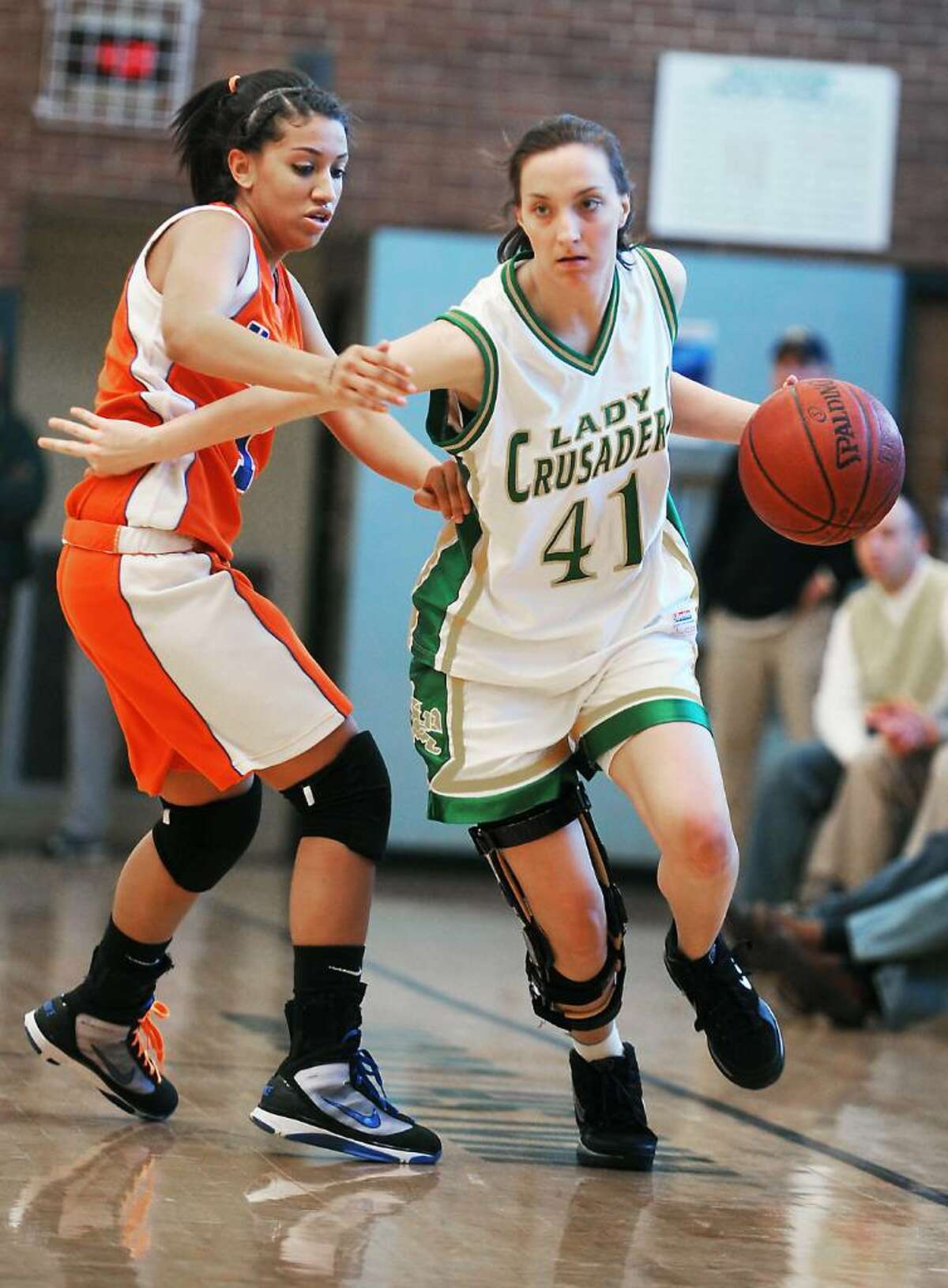 Trinity Catholic's Kelly Andersen takes the ball down the court against Danbury's Rabia Rawji in the quarterfinals of the FCIAC girls basketball championship in Stamford, Conn. on Saturday, Feb. 20, 2010.