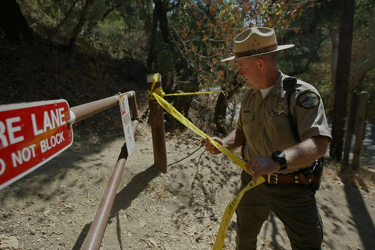 Santa Clara County Senior Park Ranger Flint Glines tapes off a hiking trail Monday, September 8, 2014 near Cupertino while crews search for a mountain lion that attacked a 6-year-old boy Sunday, September 7th, 2014