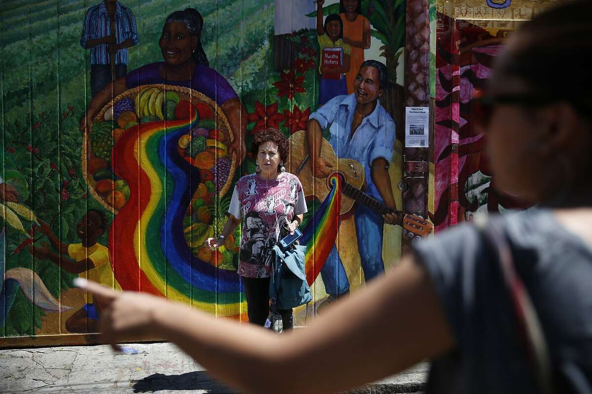 """Miranda Bergman (l to r), talks with fellow muralist, Lucia Ippolito on Balmy Alley as Ippolito passes Bergman who was working on restoring the mural """"Culture Contains the Seed of Resistance that Blossoms into the Flower of Liberation"""" (background), on Thursday, August 21, 2014 in San Francisco, Calif. """"Culture Contains the Seed of Resistance that Blossoms into the Flower of Liberation"""", painted by Miranda Bergman and O'Brien Thiele, is the last complete PLACA mural on Balmy Alley."""