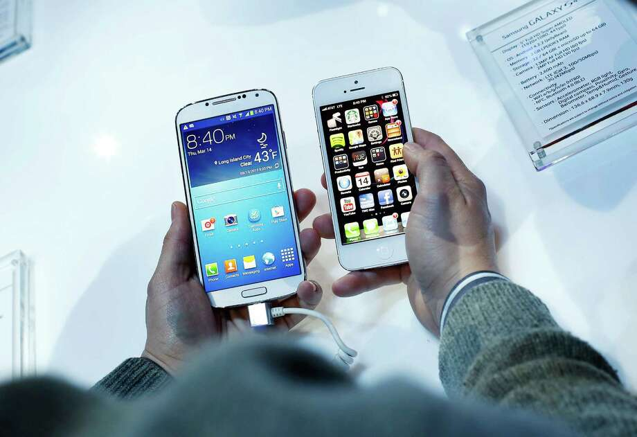 A Galaxy S4 smartphone, left, has a bigger screen than an Apple iPhone 5. Analysts expect Apple to introduce larger-screen versions of the iPhone 6. Photo: Victor J. Blue / Â 2013 Bloomberg Finance LP