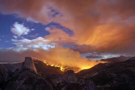 In this Sunday, Sept. 7, 2014, photo provided by Michael Frye, a wildfire burns next to Half Dome in Yosemite National Park, Calif.  As of Monday, the fire has burned through about four square miles. (AP Photo/www.michaelfrye.com)