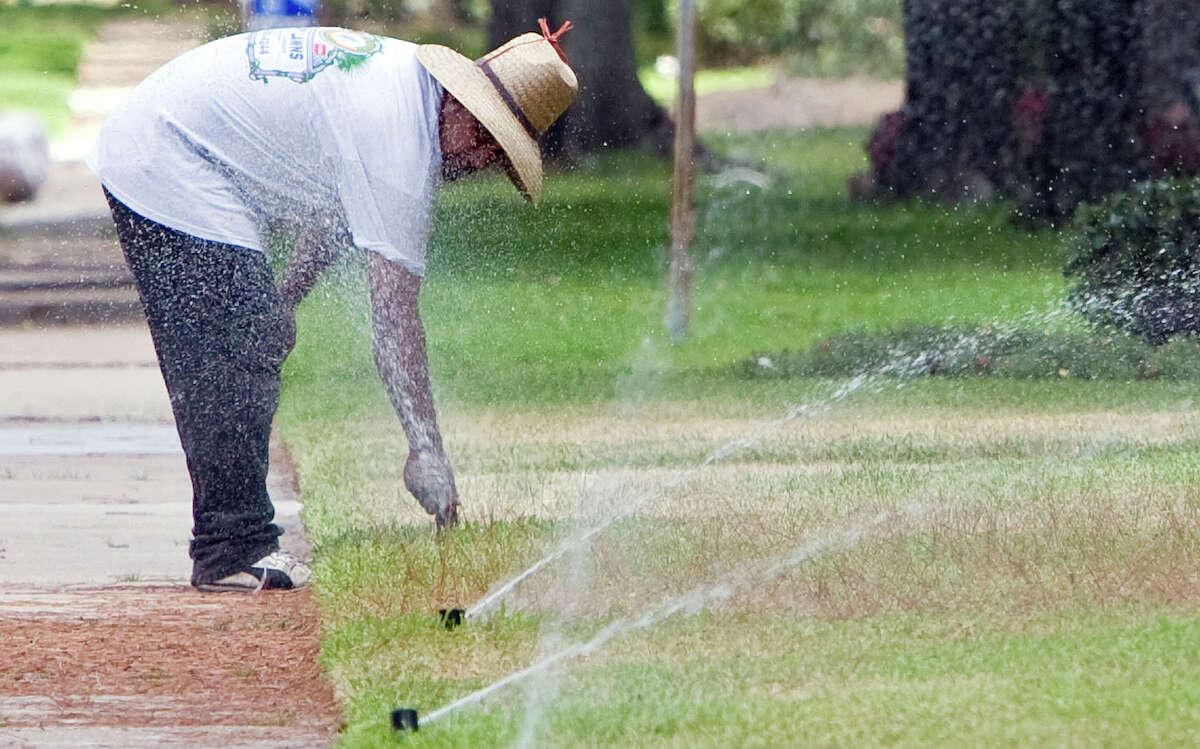 A worker adjusts a lawn sprinkler during a repair in Houston. Adjusting sprinklers helps conserve water.