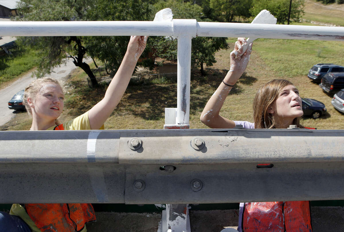 Stephanie Stockwell, 15, (left) and Kylee Caldwell, 13, paint the railing on the Guadalupe Street bridge near South Frio Street.