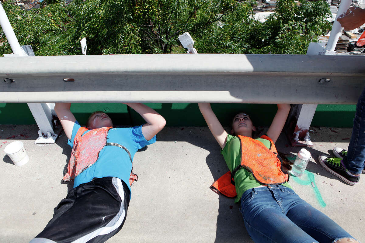 """Nate Webb and Teresa Stevens are two of about 190 youth from 14 different congregations of the Church of Jesus Christ of Latter-day Saints who participate Sept. 6, 2014 in the """"Graffiti Wipeout"""" on the Guadalupe Street bridge near S. Frio Street. All of the youth are part of the San Antonio West Stake and participated by sanding and painting the railing along the bridge as part of a service project for their church. Most of the youth are from San Antonio but some came from Uvalde, Hondo and Helotes to help out. The """"Graffiti Wipeout"""" is a partnership between the city and several other local organizations to decrease vandalism."""