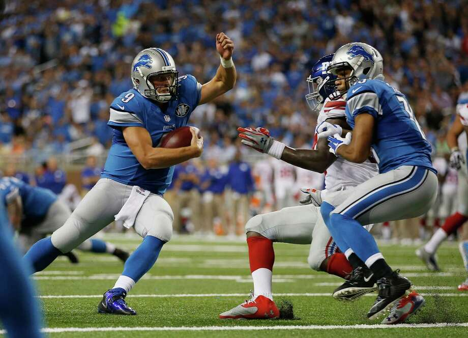 Lions quarterback Matthew Stafford, left, eludes enough Giants to score a third-quarter touchdown in Monday night's win over the Giants. Photo: Gregory Shamus, Stringer / 2014 Getty Images