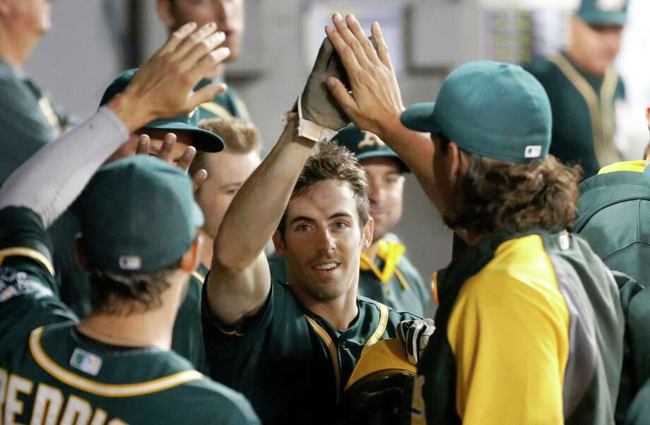 Oakland Athletics pinch runner Billy Burns celebrates in the dugout after scoring on a bunt by Sam Fuld, off a pitch from Chicago White Sox's Eric Surkamp during the eighth inning of a baseball game Monday, Sept. 8, 2014, in Chicago. (AP Photo/Charles Rex Arbogast) Photo: Charles Rex Arbogast, STF / Associated Press / AP
