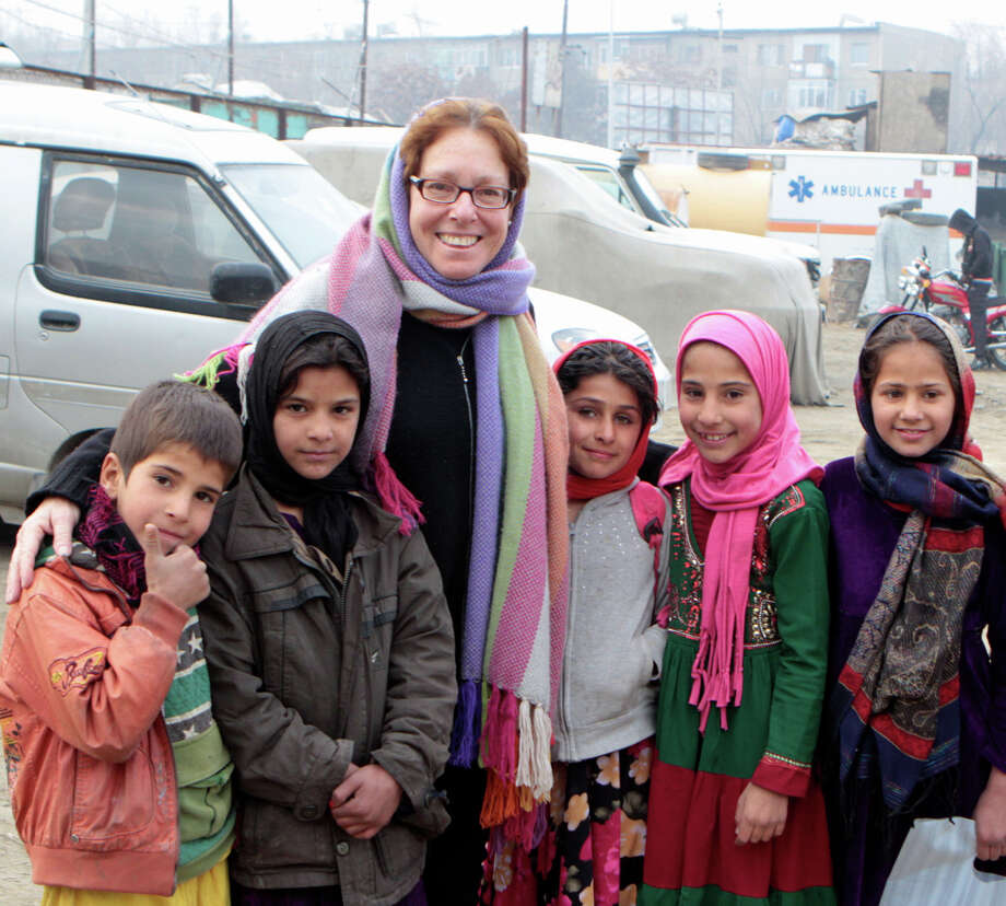 Wendy Summer, of Warren, poses with some of the children from Afghanistan she helps educate. Photo: Contributed Photo / The News-Times Contributed