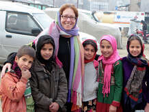 Wendy Summer, of Warren, poses with some of the children from Afghanistan she helps educate.