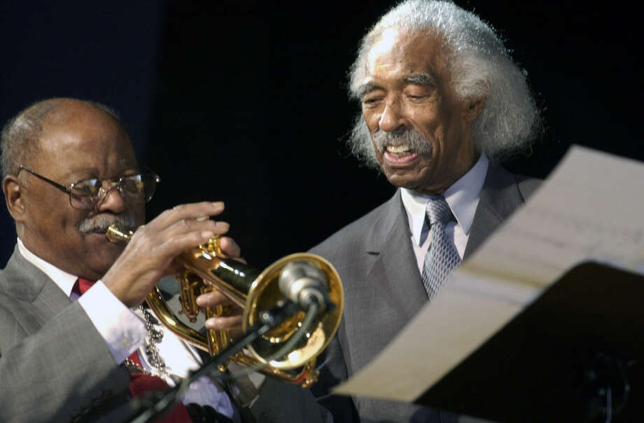 FILE - In tis Feb. 28, 2003 file photo, jazz trumpeter and former Navy band member Clark Terry, left, plays under the watchful eye of guest conductor Gerald Wilson, also a former Navy band member, at a concert at the Great Lakes Naval Training Center in Great Lakes, Ill. Wilson, the dynamic jazz big band leader, composer and arranger whose career spanned more than 75 years, died Monday, Sept. 8, 2014. He was 96. (AP Photo/Brian Kersey, File) Photo: Brian Kersey, STR / AP