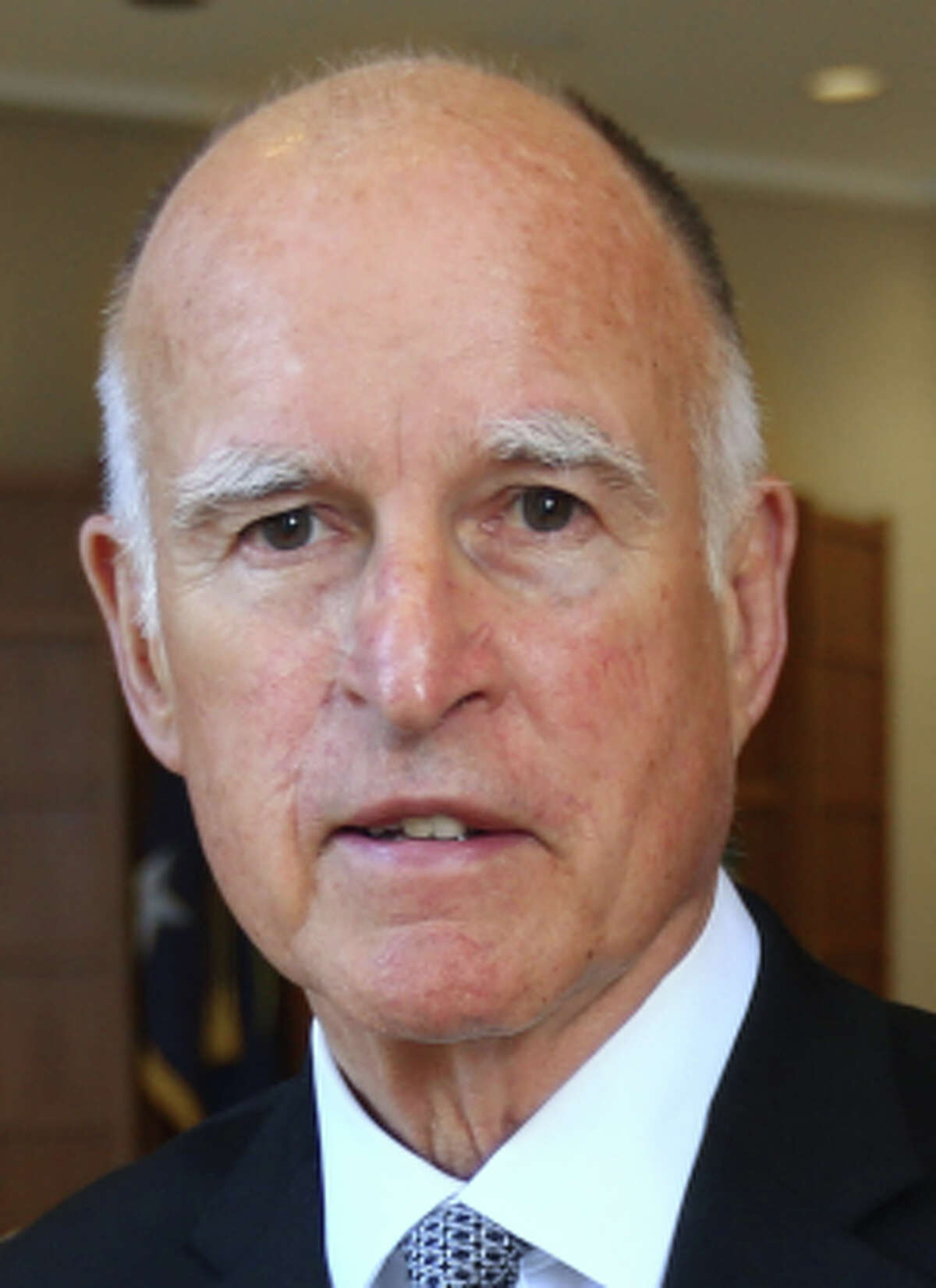 In this May 28, 2014, file photo, Gov. Jerry Brown poses in his Capitol office in Sacramento,Calif. Incumbent Brown faces Republican Neel Kashkari, a former U.S. Treasury official who has never held elective office, in the November election.