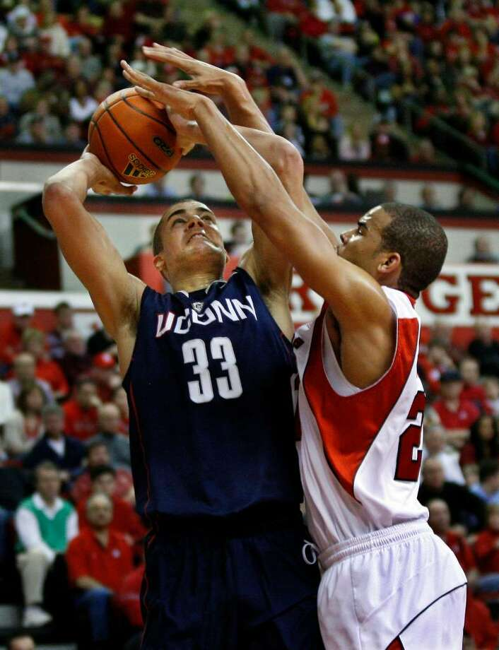 Connecticut's Gavin Edwards (33) takes a shot as Rutgers' Austin Johnson blocks his path during the second half of an NCAA college basketball game Saturday, Feb. 20, 2010, in Piscataway, N.J. Connecticut won 76-58. (AP Photo/Mel Evans) Photo: Mel Evans, AP / AP2010