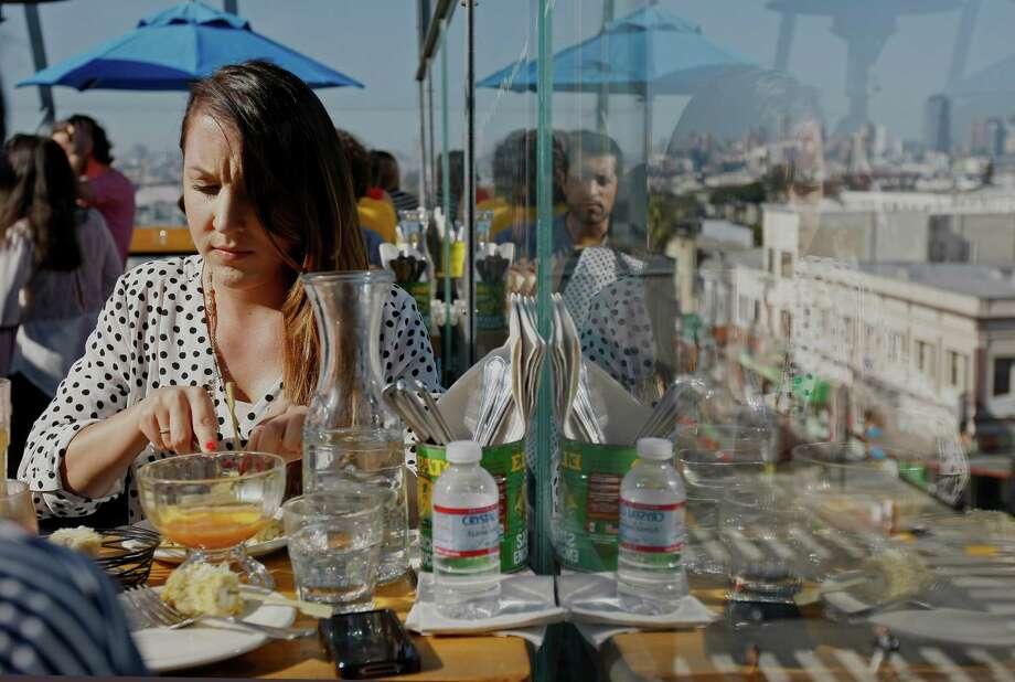 Lily Hakhpandyan sits at a table overlooking Mission Street at El Techo de Lolinda rooftop bar in the Mission. Photo: Jessica Christian, Staff Photographer / The Chronicle / ONLINE_YES