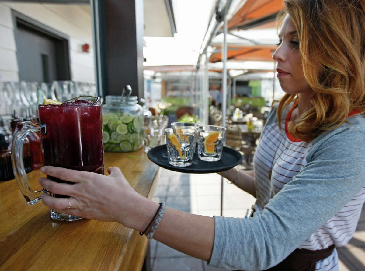 Crystal Giorgi grabs a pitcher of sangria from the bar for customers at El Techo de Lolinda rooftop bar in the Mission District.
