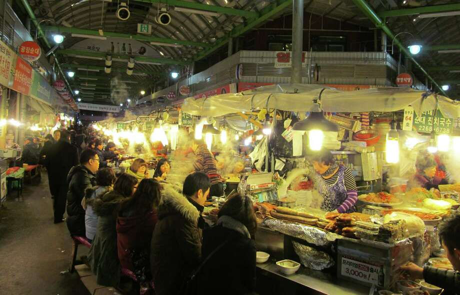 Seoul's popular Gwangjang Market is where some of the best dishes in the Korean capital are offered at cheap prices to tourists and locals alike. Photo: Amir Bibawy, STF / AP