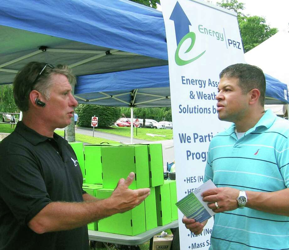 Bob Neal, left, from Energy PRZ of Brookfield offers information about the possibilities for clean energy in one's home to Ben Nunez during the Village Fair Days, July 25-26, 2014 on the Village Green in New Milford. Photo: Contributed Photo / The News-Times Contributed