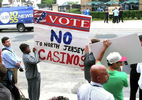 Protestors hold signs across the street from a meeting New Jersey Gov. Chris Christie convened on Monday on the future of Atlantic City, hours after Christie's administration said it will allow the casinos and horse tracks to offer sports betting. Photo: Associated Press / AP