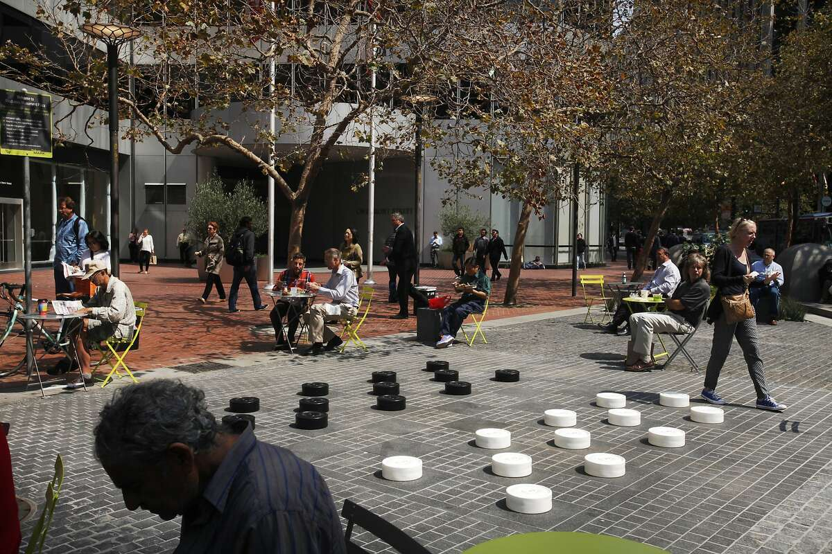 People listen to music as they eat lunch and pass through the recently refinished Mechanics Plaza Sept. 9, 2014 in San Francisco, Calif. Tables and chairs were added to the space as well as a large checkers/chess board design on the ground. The band Dos Gardenias played music at noon as part of the People in the Plazas Summer Music Festival.