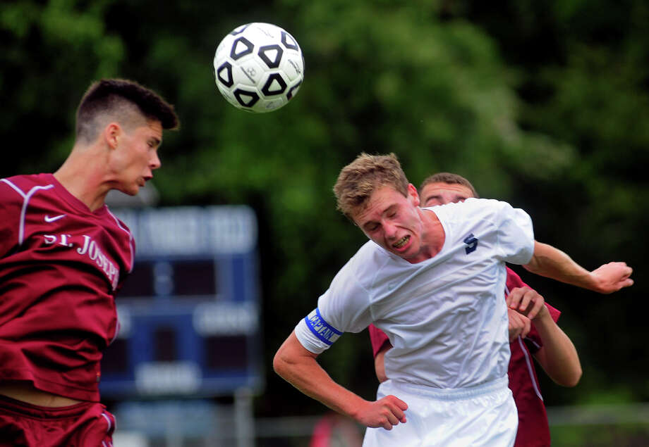 Staples captain Patrick Beusse, right, heads the ball with St. Joseph's Christian Barroso looking to intercept, during boys high school soccer action in Westport, Conn. on Tuesday September 9, 2014. Photo: Christian Abraham / Connecticut Post