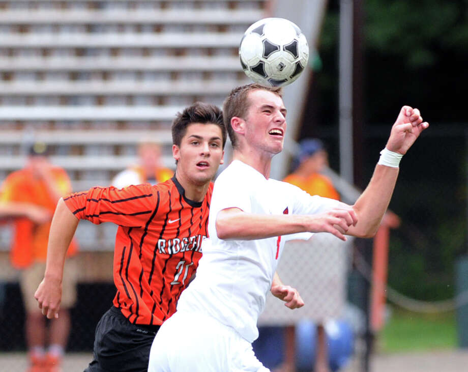 At right, Nick Bartels of Greenwich heads the ball while attacking as Ridgefield's Andrew Papa (#21) defends during the boys high school soccer match between Greenwich High School and Ridgefield High School at Greenwich, Conn., Tuesday, Sept. 9, 2014. Bartels scored three goals as Greenwich defeated Ridgefield, 3-0. Photo: Bob Luckey / Greenwich Time