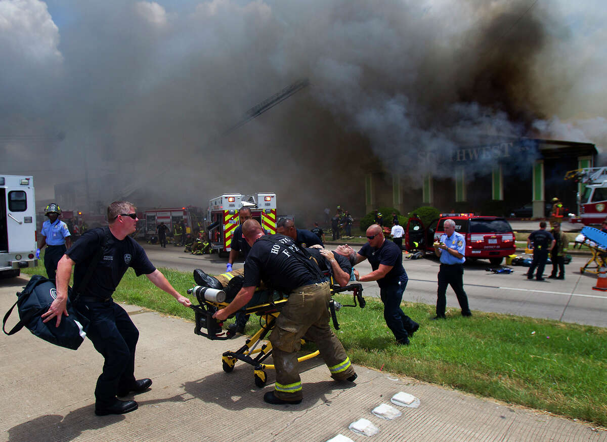 FILE - In this May 31, 2013 file photo, a firefighter injured while fighting a fire at the Southwest Inn in Houston is wheeled to an ambulance. (AP Photo/Houston Chronicle, Cody Duty, File) MANDATORY CREDIT