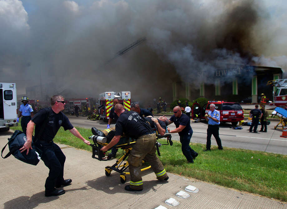 FILE - In this May 31, 2013 file photo, a firefighter injured while fighting a fire at the Southwest Inn in Houston is wheeled to an ambulance. (AP Photo/Houston Chronicle, Cody Duty, File) MANDATORY CREDIT Photo: Cody Duty, MBI / Houston Chronicle