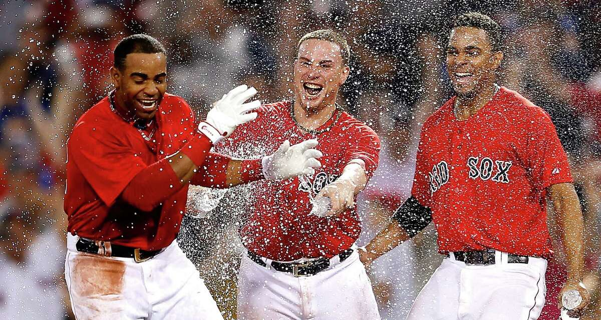 Yoenis Céspedes (left) celebrates with Christian Vazquez and Xander Bogaerts after one of his big Red Sox moments.