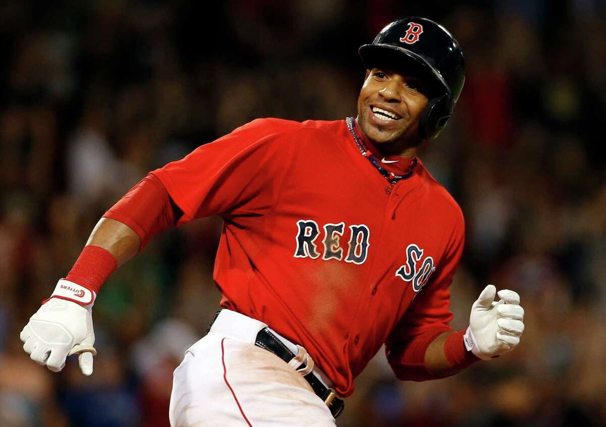 Boston Red Sox's Yoenis Cespedes smiles at teammates charging out of the dugout after hitting the game-winning RBI single against the Toronto Blue Jays during the 10th inning of the Red Sox's 9-8 win in a baseball game at Fenway Park in Boston on Friday, Sept. 5, 2014. (AP Photo/Winslow Townson)