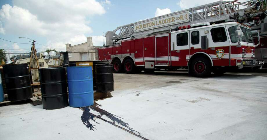 Chemicals leak from barrels Tuesday at the City of Houston Fire Department Logistical Center and Maintenance Depot at 1205 Dart. A recent inspection echoed many of the same problems cited three years ago fire inspector report. Photo: Billy Smith II, Staff / © 2014 Houston Chronicle