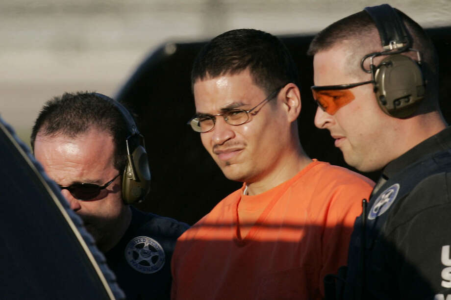 """FILE - In this Jan. 5, 2006 file photo, Jose Padilla, center, is escorted to a waiting police vehicle by federal marshals near downtown Miami. Padilla is set to be sentenced a second time by a federal judge Tuesday, Sept. 9, 2014 in Miami, because the original prison term of 17 years was too lenient. Padilla was arrested by the FBI in 2002 on what authorities said was an al-Qaida mission to detonate a radioactive """"dirty bomb"""" inside the U.S. Those accusations were later discarded. (AP Photo/J. Pat Carter, File) Photo: J. PAT CARTER, STF / AP"""