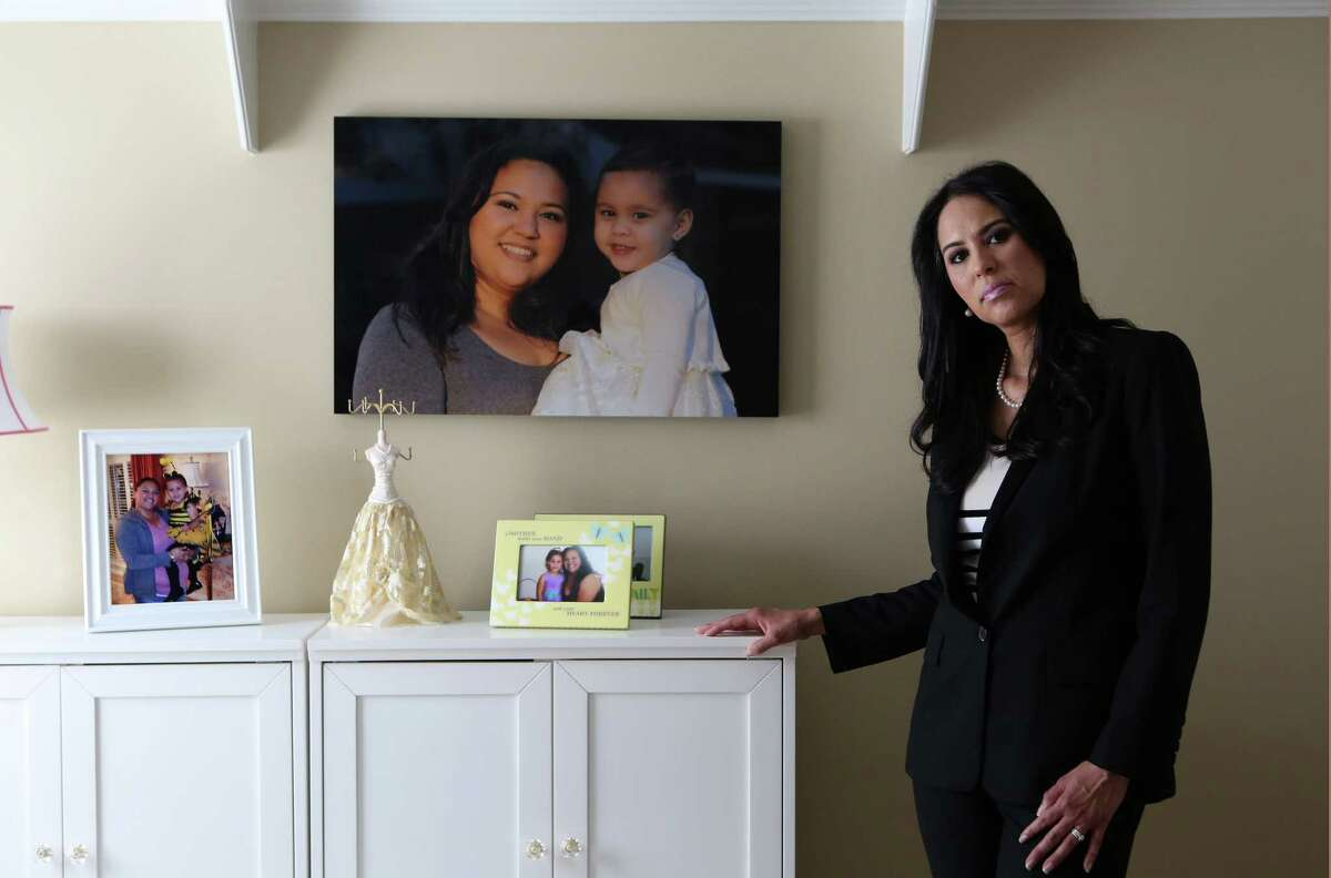Lisa Forsythe stands next to a photograph of her sister, Linda Alton, who was killed by her ex-boyfriend in May 2012, five months after a judge denied her request for a protective order. He shot her several times in front of their 2-year-old daughter before turning the gun on himself. Forsythe got primary custody of her niece, also pictured, after the death of her parents. Alton's story is one of many included in a report released Tuesday that details a drastic decline in the number of protective orders being granted to Harris County women since 2011. ( Mayra Beltran / Houston Chronicle )