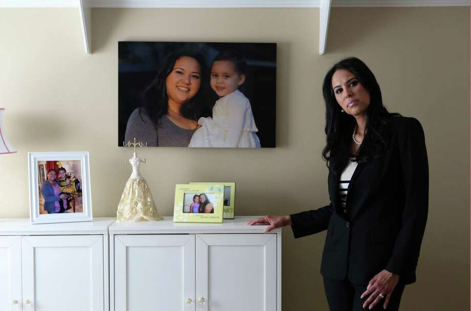 Lisa Forsythe stands next to a photograph of her sister, Linda Alton, who was killed by her ex-boyfriend in May 2012, five months after a judge denied her request for a protective order. He shot her several times in  front of their 2-year-old daughter before turning the gun on himself. Forsythe got primary custody of her niece, also pictured, after the death of her parents. Alton's story is one of many included in a report released Tuesday that details a drastic decline in the number of protective orders being granted to Harris County women since 2011. (  Mayra Beltran / Houston Chronicle ) Photo: Mayra Beltran, Staff / © 2014 Houston Chronicle