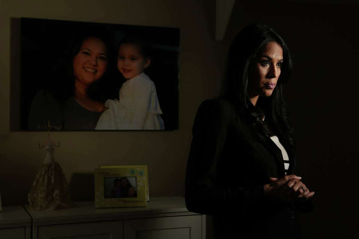 Lisa Forsythe stands next to a photograph of her sister holding her daughter which she has primary custody of her niece after her parents died two years ago on Thursday, Sept. 4, 2014, in Houston. Linda Alton, was killed by her ex-boyfriend in May 2012, five months after this judge denied her protective orders application. He shot her several times in front of their 2-year-old daughter before turning the gun on himself. ( Mayra Beltran / Houston Chronicle )