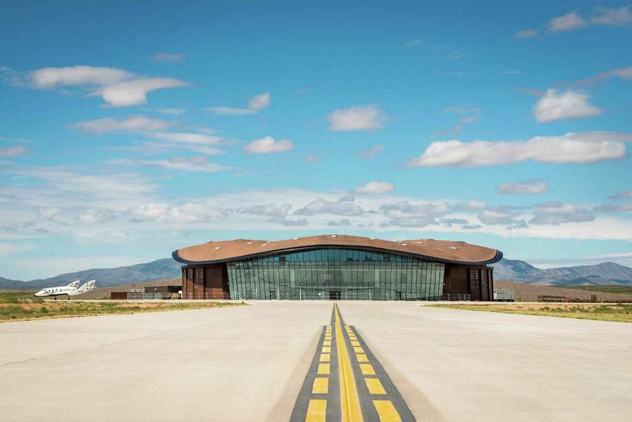 A mockup of Spaceship Two sits next to the Virgin Galactic's Gateway To Space building at Spaceport America in New Mexico. A new study suggests that people with common illnesses can travel safely in space. Photo: Smiley N. Pool, Houston Chronicle / © 2014  Houston Chronicle