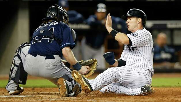 New York Yankees' Stephen Drew, right, is tagged out at the plate by Tampa Bay Rays catcher Ryan Hanigan (24) during the fifth inning of a baseball game at Yankee Stadium in New York, Tuesday, Sept. 9, 2014. Yankees manager Joe Girardi requested a video review of the play, but the ruling on the field was upheld. (AP Photo/Kathy Willens) ORG XMIT: NYY110 Photo: Kathy Willens / AP