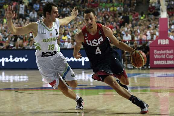 US guard Stephen Curry (R) vies with Slovenia's guard Domen Lorbek (L) during the 2014 FIBA World basketball championships quarter-final match Slovenia vs USA at the Palau Sant Jordi arena in Barcelona on September 9, 2014.  AFP PHOTO / LLUIS GENELLUIS GENE/AFP/Getty Images