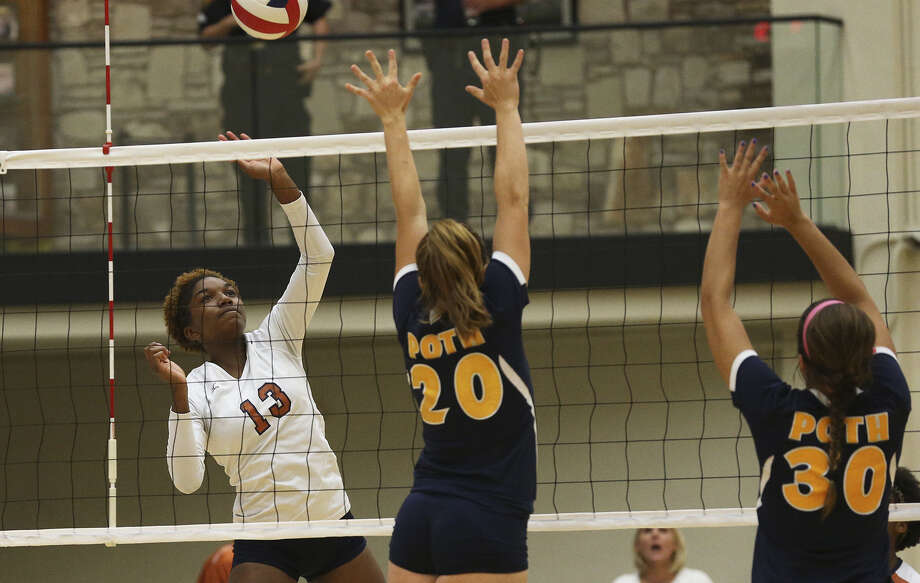 Madison's Malaezha Carter (left), going up for a shot over Poth's Ahnika McPherson (center) and Madison Caloss, had two kills during a key stretch for the Mavericks in the third set. Photo: Tom Reel / San Antonio Express-News