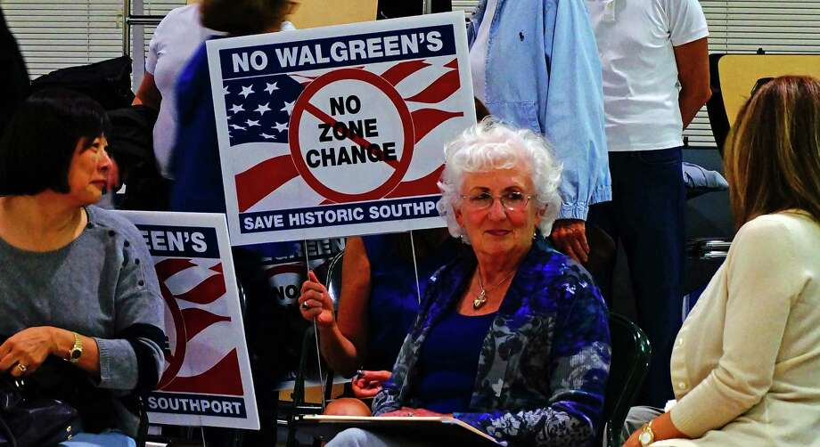 Residents opposed to a Walgreen's on the Post Road near the Westport town line brought their lawn signs with them to the Town Plan and Zoning hearing Tuesday night. Photo: Genevieve Reilly / Fairfield Citizen