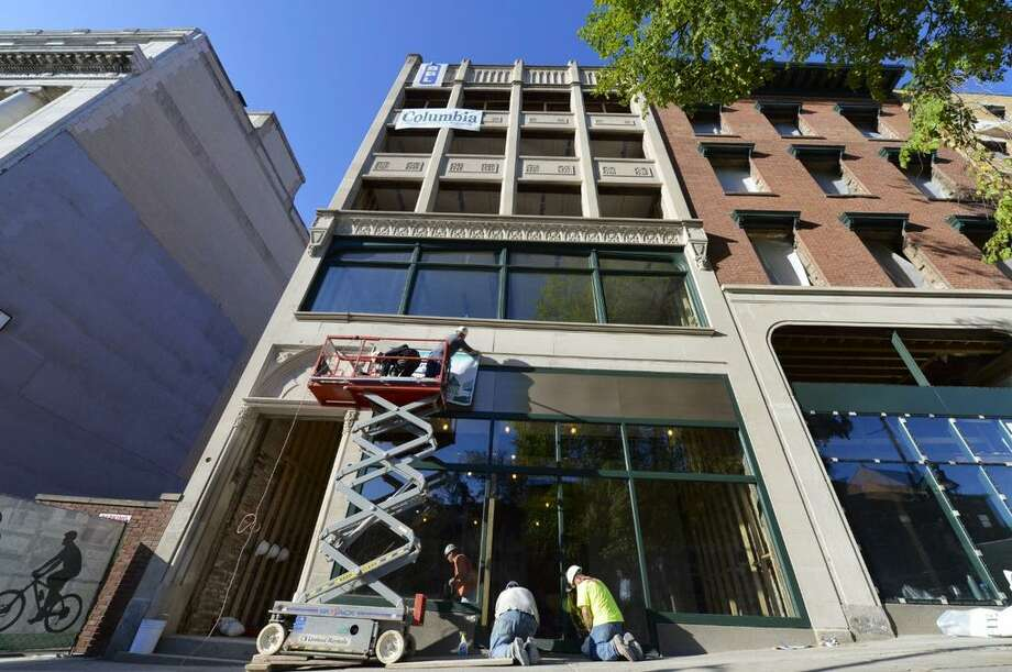Workers affix a Capital Bank sign on Wellington Row before a press conference Wednesday at 132 State St., Albany. (Skip Dickstein/Times Unon)